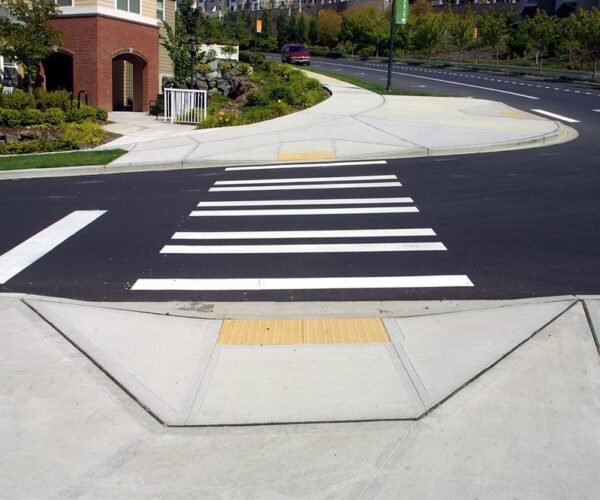 Proper curb ramps with tactile warning strip indicator identifying vehicle traffic lane for low vision users